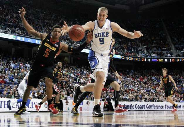 Duke's Mason Plumlee, right, and Maryland's Nick Faust, left, chase a loose ball during the first half of an NCAA college basketball game at the Atlantic Coast Conference men's tournament in Greensboro, N.C., Friday, March 15, 2013. (AP Photo/Gerry Broome) Photo: Gerry Broome