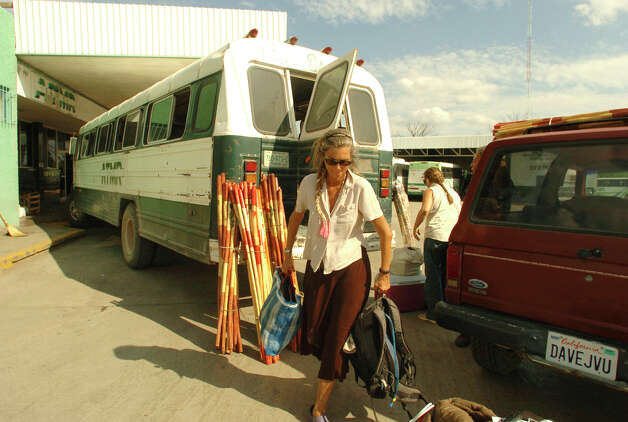 After a long bus ride, Cynta de Narvaez unloads quilts and other merchandise made by residents of Boquillas  del Carmen in Muzquiz, Mexico. The items will eventually be sold in Big Bend National Park. The residents of Boquillas once made a very good living by providing meals, beer and curios to tourists and hikers visiting the Big Bend of Texas. There was no official border crossing, but tourists were unofficially allowed to cross the Rio Grande, spend time and money in Boquillas, and return. All of this changed in 2002, when, in response to the Sept. 11 attacks, the crossing was closed as part of a crackdown on the borders. Since then, Boquillas has been shrinking because residents of this extremely isolated town have have almost no income. Photo: BILLY CALZADA, San Antonio Express-News / SAN ANTONIO EXPRESS-NEWS