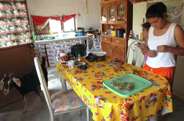 Carina Ureste, 14, stands in the kitchen of her family's modest Boquillas del Carmen, Mexico, home in October 2006, making copper scorpion earrings that will be sold in the Big Bend National Park. Photo: BILLY CALZADA, San Antonio Express-News / SAN ANTONIO EXPRESS-NEWS