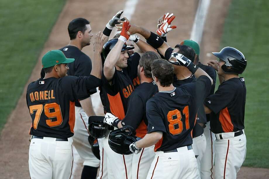 Giants players celebrate with Cole Gillespie (center, red gloves) after hitting a walk-off home run to win a spring training baseball game against the Colorado Rockies on March 17, 2013 in Scottsdale, Arizona. Photo: Pete Kiehart, The Chronicle