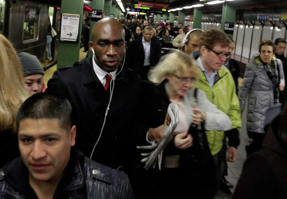 "In this photo taken March 14, 2013, morning commuters fill the platform as they exit a train in New York's Times Square subway station. An historic decline in the number of U.S. whites and the fast growth of Latinos are blurring traditional black-white color lines, testing the limits of civil rights laws and reshaping political alliances as ""whiteness"" begins to lose its numerical dominance. The demographic shift is now a potent backdrop to an immigration overhaul bill being debated in Congress that could offer a path to citizenship for 11 million mostly Hispanic illegal immigrants.  (AP Photo/Richard Drew) Photo: Richard Drew"