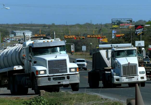 Truck traffic related to the Eagle Ford Shale energy boom travels through Kenedy on Friday. The boom has also stressed the area's roads and housing. Photo: Billy Calzada, Staff / San Antonio Express-News