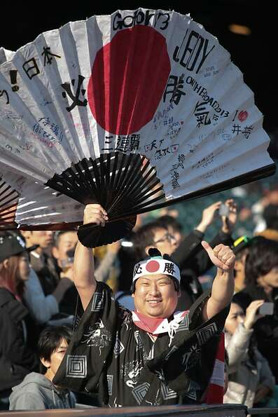 A fan signals to team Japan players before the start of the World Baseball Classic semi-final game b