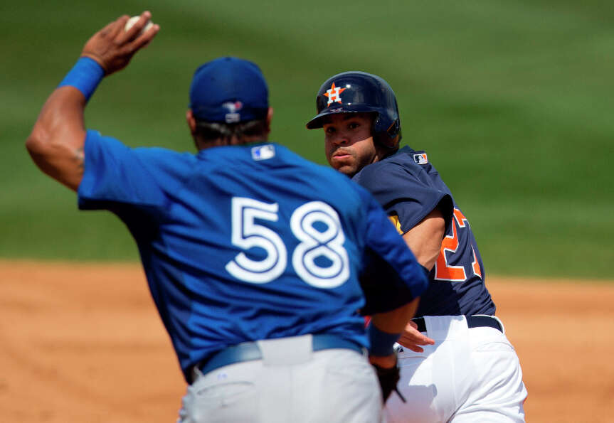Blue Jays infielder Luis Jimenez, left, chases Jose Altuve during a rundown in the fifth inning.