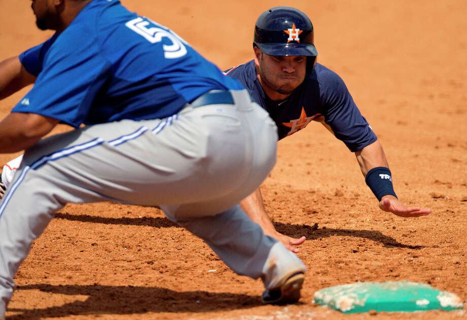 Jose Altuve dives back to first base during the third inning on Sunday in Kissimmee, Fla. Photo: Evan Vucci