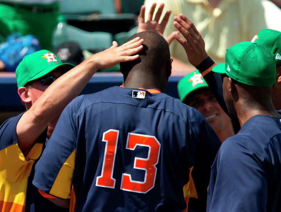 Chris Carter (13) is congratulated by members of the coaching staff after hitting his second home run. Photo: Evan Vucci