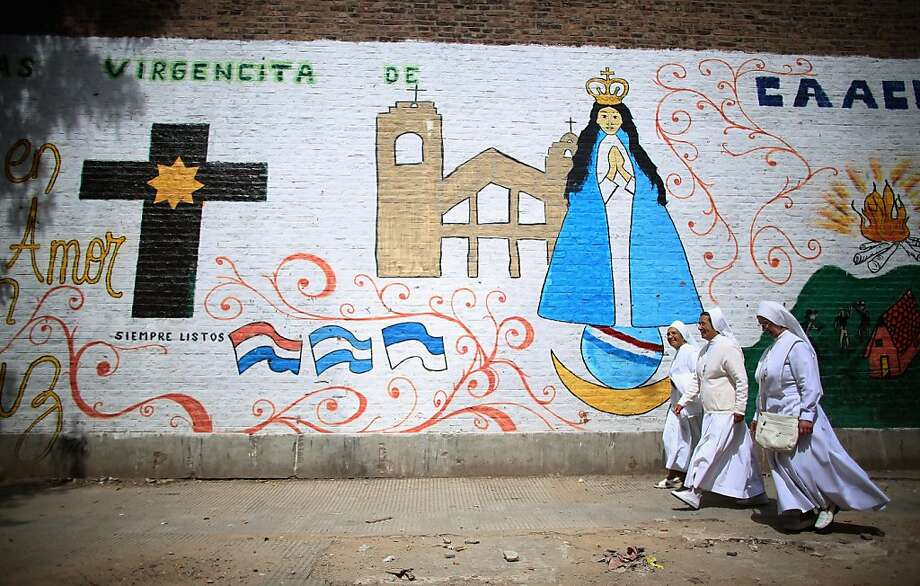 Nuns walk past a mural near the Virgin of the Miracles of Caacupe church following Sunday Mass in the Villa 21-24 slum, where archbishop Jorge Mario Bergoglio, now Pope Francis, used to perform charity work, on March 17, 2013 in Buenos Aires, Argentina. Francis was the archbishop of Buenos Aires and is the first Pope to hail from South America. Some locals are now affectionately calling Francis, known for his charity work in the slums, the 'slum pope.' Photo: Mario Tama, Getty Images