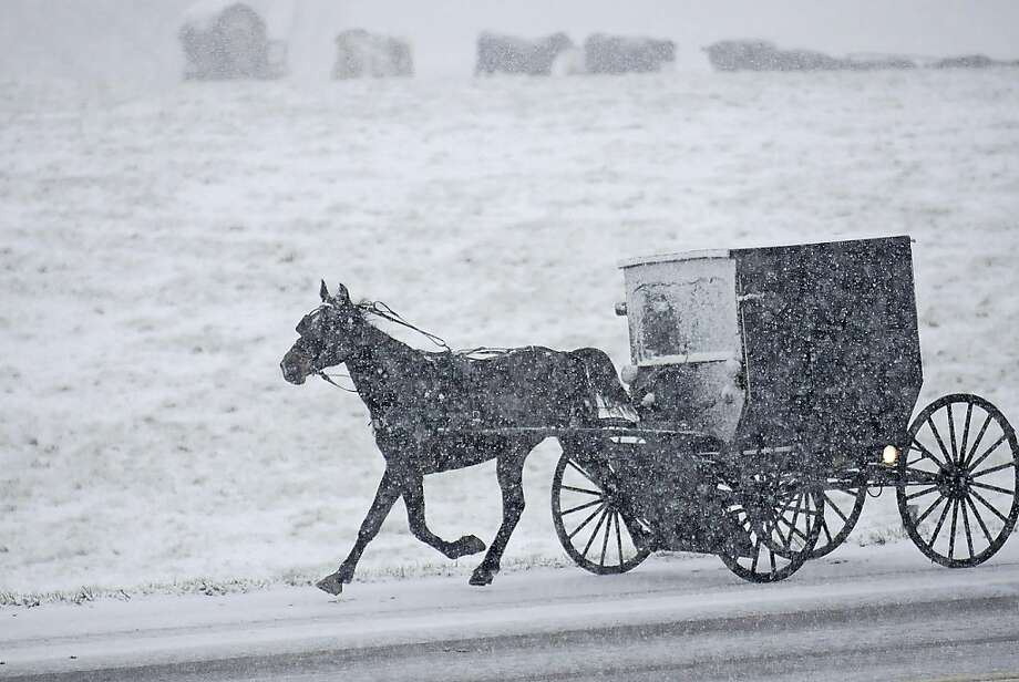 Snow falls early Sunday, March 17, 2013, as an Amish family travels to church services near Maysville, Ky.  Photo: Terry Prather, Associated Press