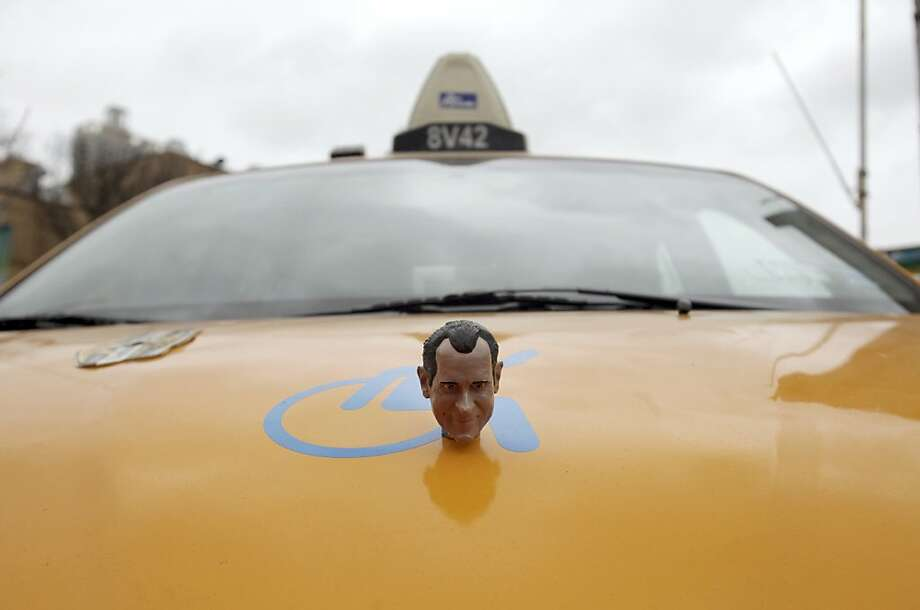 A hood ornament made from a Richard Nixon bobblehead doll on artist Daniel Wilson's taxi in New York, March 6, 2013. Wilson, a documentary filmmaker and licensed cabby, secretly recorded the conversations of his passengers, assembled the highlights into an audio collage and installed the final product in his taxi.  Photo: Hiroko Masuike, New York Times