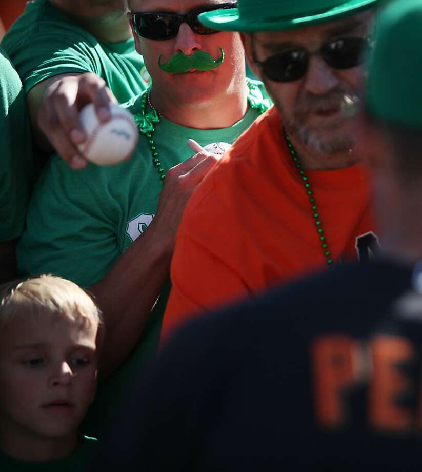 Giants fans, including Bryan Sharp, (green mustache) of Roseville, Calif., attempt to get memorabilia autographed by Hunter Pence at a spring training baseball game against the Colorado Rockies on March 17, 2013 in Scottsdale, Arizona. Many fans wore green, and both teams donned green caps, in honor of St. Patrick's Day. Photo: Pete Kiehart, The Chronicle