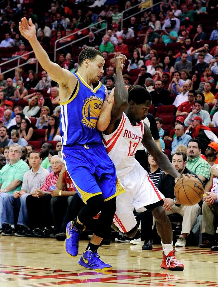 Stephen Curry, left, Patrick Beverley tangle in the second half. Photo: Pat Sullivan
