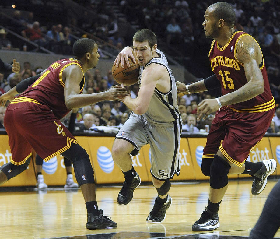 Spurs guard Nando De Colo drives between Cleveland's C.J. Miles (left) and Marreese Speights during the Spurs' 119-113 victory Saturday at the AT&T Center. Photo: Billy Calzada / Express-News