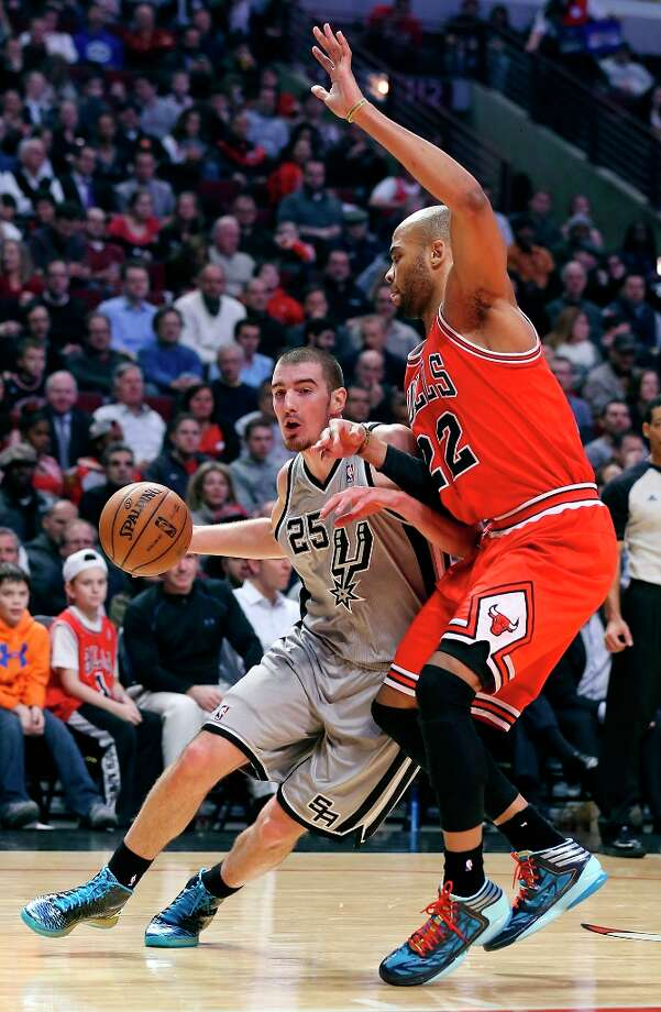 The Spurs' Nando De Colo looks for room around Chicago Bulls' Taj Gibson during first half action Monday, Feb. 11, 2013 at the United Center in Chicago. Photo: Edward A. Ornelas, San Antonio Express-News / © 2013 San Antonio Express-News