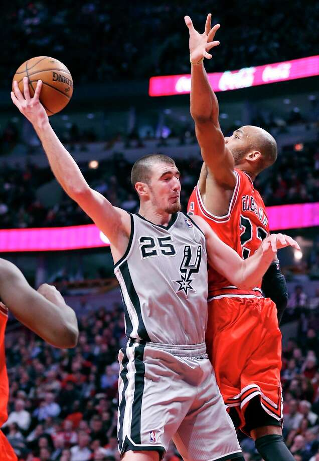 The Spurs' Nando De Colo passes around Chicago Bulls' Taj Gibson during second half action Monday, Feb. 11, 2013 at the United Center in Chicago. The Spurs won 103-89. Photo: Edward A. Ornelas, San Antonio Express-News / © 2013 San Antonio Express-News
