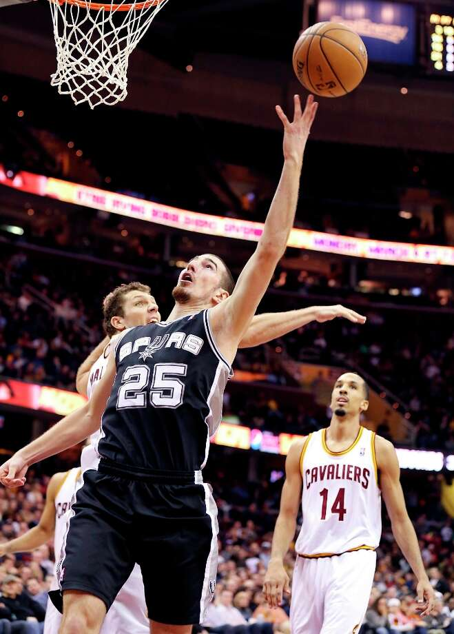 The Spurs' Nando De Colo shoots around Cleveland Cavaliers' Luke Walton as the Cavaliers' Shaun Livingston looks on  during second half action Wednesday, Feb. 13, 2013 at the Quicken Loans Arena in Cleveland, Ohio. The Spurs won 96-95. Photo: Edward A. Ornelas, San Antonio Express-News / © 2013 San Antonio Express-News