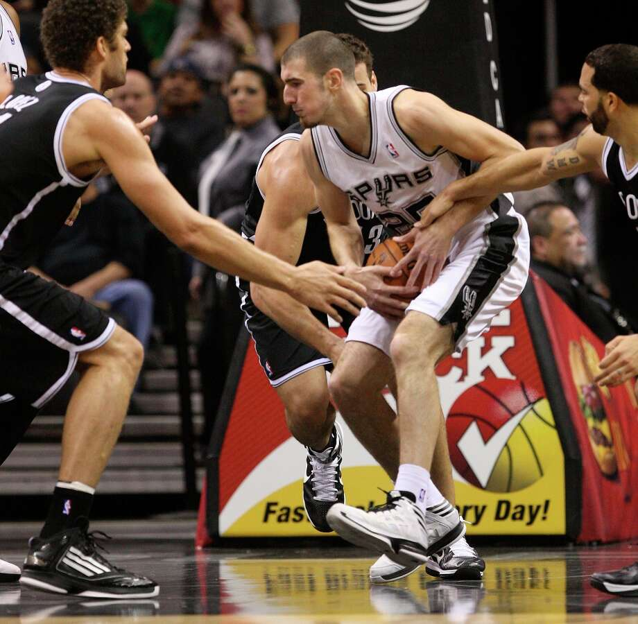 The Spurs' Nando De Colo grabs a rebound between Brooklyn Nets' (from left) Brook Lopez, Kris Humphries and Deron Williams during the first half at the AT&T Center, Monday, Dec. 31, 2012. Photo: Jerry Lara, San Antonio Express-News / © 2012 San Antonio Express-News