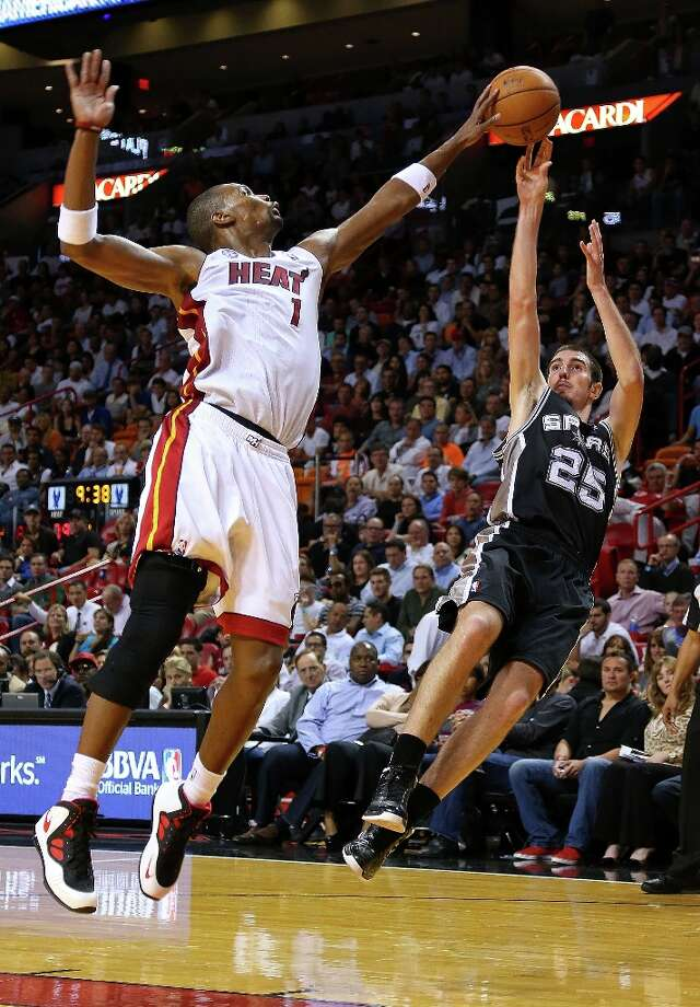 Chris Bosh (1) of the Heat blocks a shot from Nando de Colo (25) of the Spurs during a game  at American Airlines Arena on Nov. 29, 2012 in Miami. Photo: Mike Ehrmann, Getty Images / 2012 Getty Images
