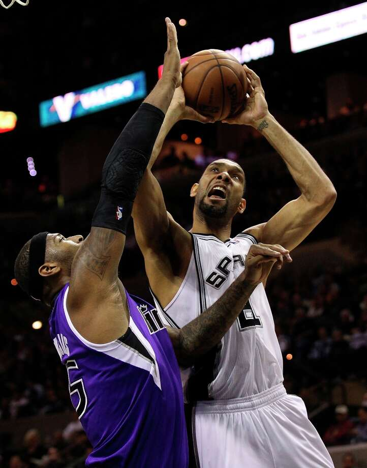 The Spurs' Tim Duncan (21) shoots against Sacramento Kings' DeMarcus Cousins (15) in the first half at the AT&T Center on Friday, Mar. 1, 2013. Photo: Kin Man Hui, San Antonio Express-News / © 2012 San Antonio Express-News