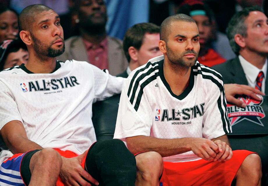 The West's Tim Duncan and Tony Parker watch second half action of the 62nd All-Star game against the East from the bench at the Toyota Center Sunday Feb. 17, 2013 in Houston. The West won 143-138. Photo: Edward A. Ornelas, San Antonio Express-News / © 2013 San Antonio Express-News
