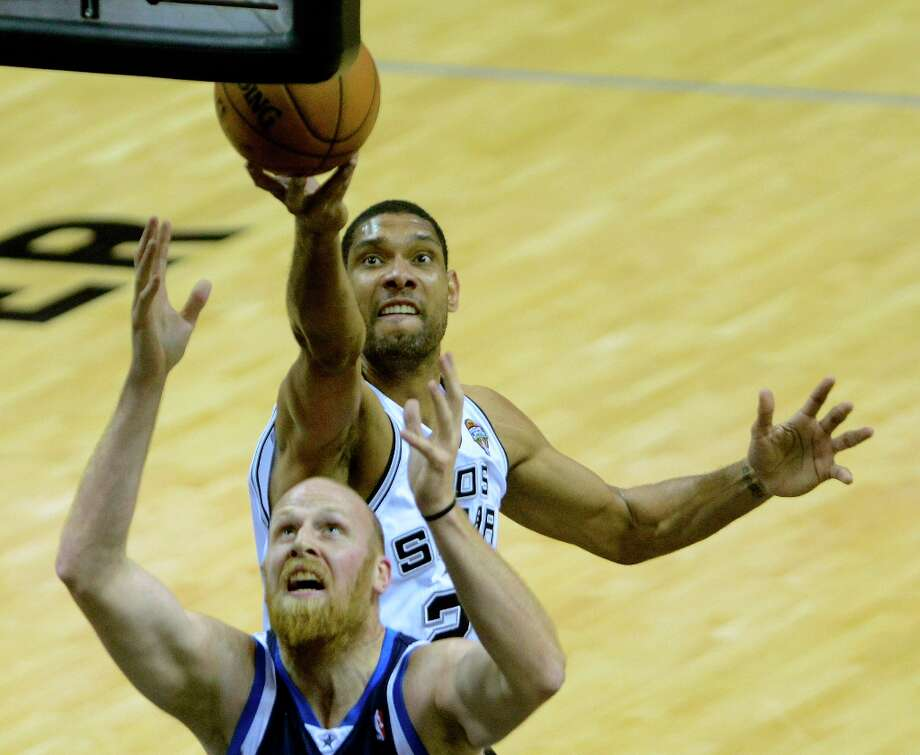 Tim Duncan of the Spurs rebounds over Chris Kaman of the Dallas Mavericks during NBA action at the AT&T Center on Thursday, March 14, 2013. Photo: Billy Calzada, San Antonio Express-News / San Antonio Express-News