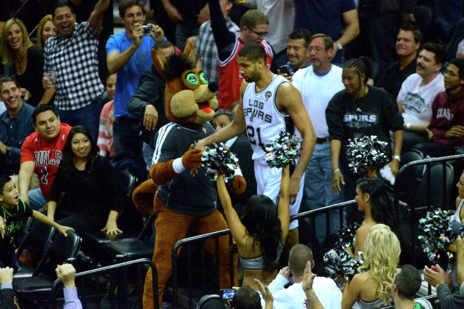 Tim Duncan of the Spurs is greeted by the Coyote mascot and fans after his momentum caused him to run into the stands during play against the Chicago Bulls at the AT&T Center on Wednesday, March 6, 2013. Photo: Billy Calzada, San Antonio Express-News / San Antonio Express-News