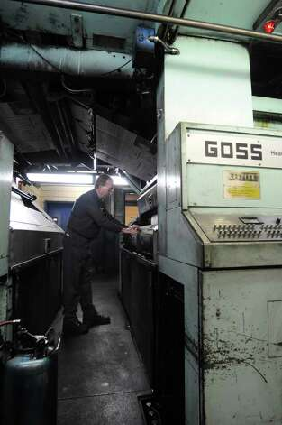 Al Veve, pressman in charge, attaches a printing plate to a roller on the Goss letter press in the pressroom at the Times Union in Colonie, NY on Monday, March 31, 2008. Veve, who started in the maintenance department at the Times Union in 1968, helped unload this press at the paper before it was installed.  In 1971 Veve moved into a job in the pressroom.  (Paul Buckowski/Times Union) Photo: Paul Buckowski / Albany Times Union