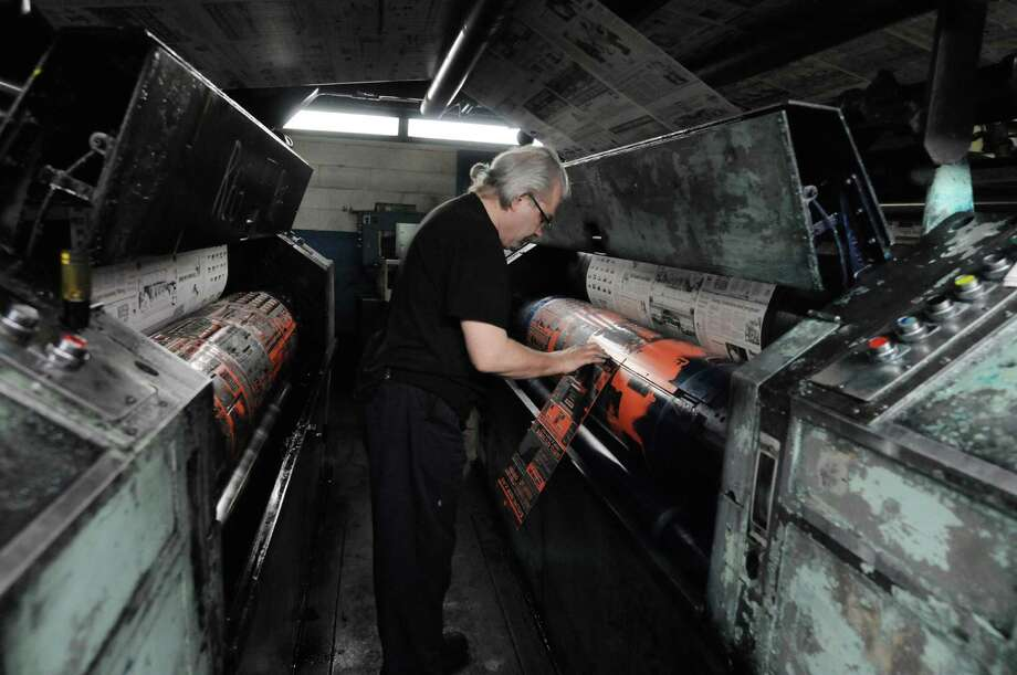 Times Union pressman Bob Barron makes registration adjustments to one of the color plates early Sunday morning, Feb. 17, 2013, at the Times Union in Colonie, N.Y. The Goss Headliner press was installed in 1970. (Will Waldron/Times Union) Photo: Will Waldron