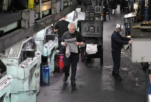 Times Union pressmen Bob Barron, left, and Robert Care, right, examine newsprint for registration color correction early Sunday morning, Feb. 17, 2013, at the Times Union in Colonie, N.Y. Press operators constantly examine print and make adjustments to the press during the entire run. The Times Union?s Goss Headliner press was installed in 1970. (Will Waldron/Times Union) Photo: Will Waldron