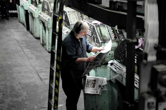 Times Union pressmen Mike  Swiecicki examines newsprint for registration color correction early Sunday morning, Feb. 17, 2013, at the Times Union in Colonie, N.Y. Press operators constantly examine print and make adjustments to the press during the entire run. The Times Union?s Goss Headliner press was installed in 1970. (Will Waldron/Times Union) Photo: Will Waldron