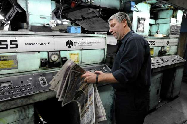Times Union pressman Robert Bottari makes color adjustments to the press early Sunday morning, Feb. 17, 2013, at the Times Union in Colonie, N.Y. Press operators constantly examine print and make adjustments to the press during the entire run. The Times Union?s Goss Headliner press was installed in 1970. (Will Waldron/Times Union) Photo: Will Waldron