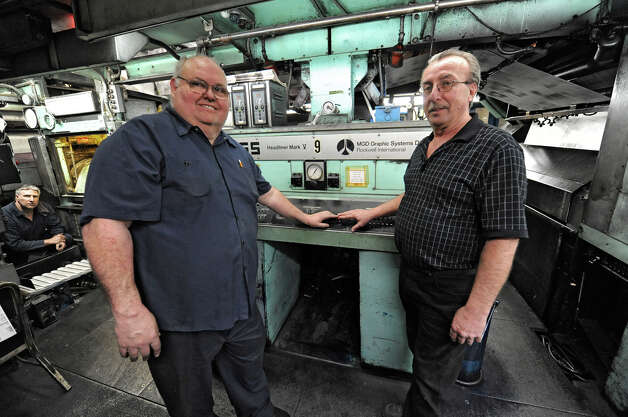 Pressmen Tom Wagoner, left, and Al Veve press the stop button for the final time after the last run of the old Goss press at the Times Union on Monday, March 18, 2013 in Colonie, N.Y.  (Lori Van Buren / Times Union) Photo: Lori Van Buren