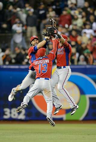 Alex Rios, Jesus Feliciano (13) and Angel Pagan (16) of Team Puerto Rico celebrate defeating Team Japan. Photo: Thearon W. Henderson, Getty Images