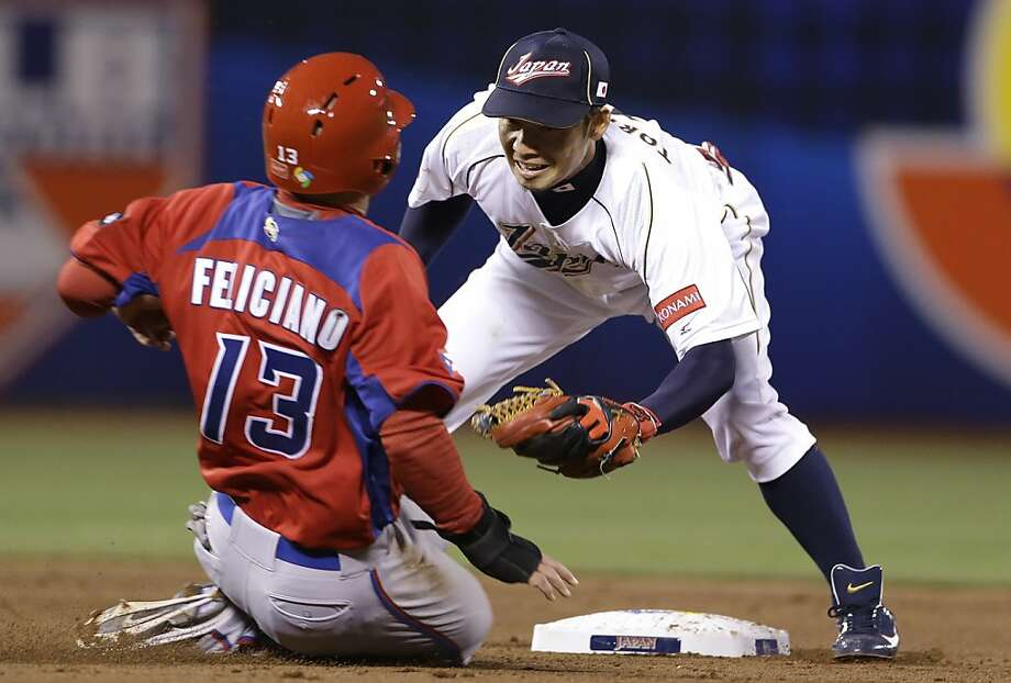 Japan's Takashi Toritani, right, waits to tag out Puerto Rico's Jesus Feliciano trying to steal second base during the fifth inning of a semifinal game of the World Baseball Classic in San Francisco, Sunday, March 17, 2013. Photo: Eric Risberg, Associated Press