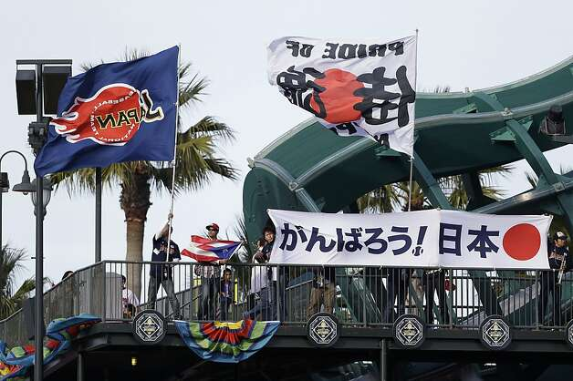 Japanese and Puerto Rican fans hold signs and flags during a semifinal game of the World Baseball Classic between Japan and Puerto Rico in San Francisco, Sunday, March 17, 2013. Photo: Eric Risberg, Associated Press