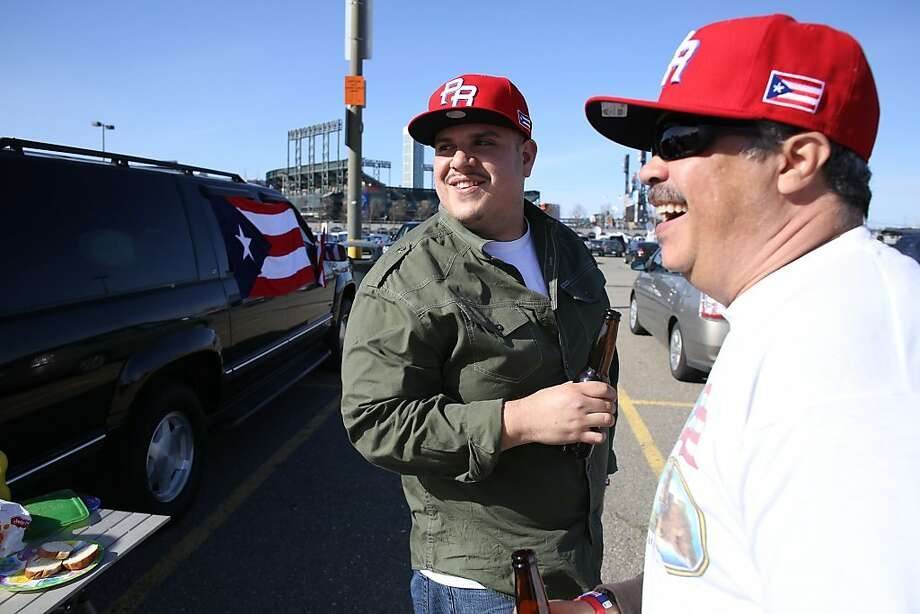 Hector Monge, right, and Jesus Anguiano tailgate before the start of the World Baseball Classic semi-final game between Puerto Rico and Japan in San Francisco on Sunday, March 17, 2013. Photo: Mathew Sumner, Special To The Chronicle
