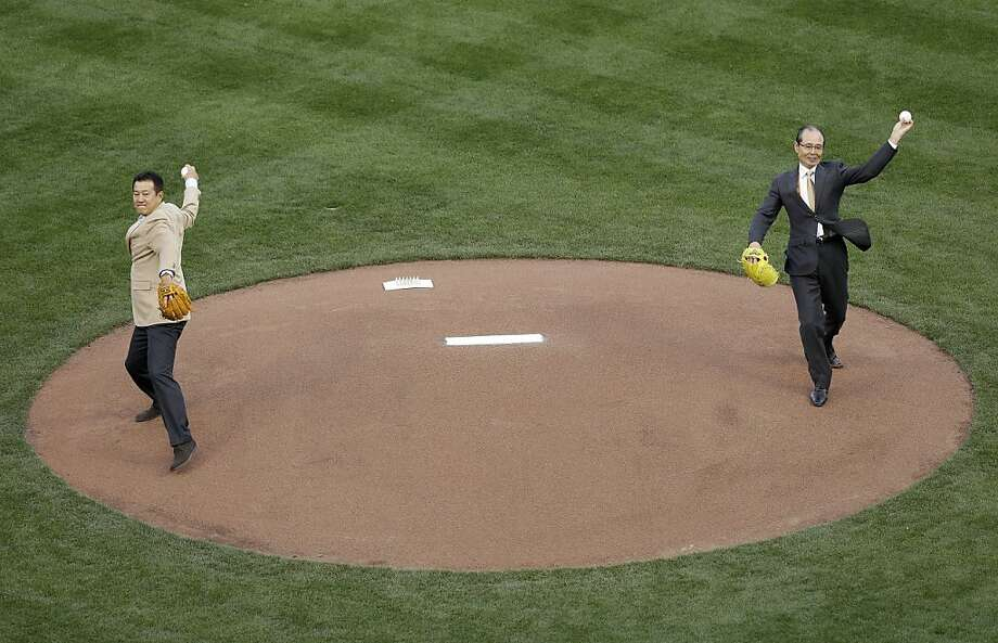 Former baseball players Tatsunori Hara, left, and Sadaharu Oh throw out the ceremonial first pitch before a semifinal game of the World Baseball Classic between Japan and Puerto Rico in San Francisco, Sunday, March 17, 2013. Photo: Jeff Chiu, Associated Press