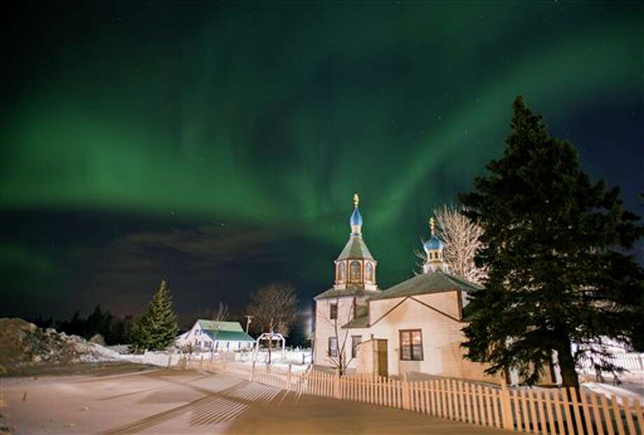 The aurora borealis, or northern lights, fill the sky early Sunday, March 17, 2013, above the Holy Assumption of the Virgin Mary Russian Orthodox church in Kenai, Alaska. The bright display at times filled the sky. (AP Photo/M. Scott Moon) Photo: M. SCOTT MOON, ASSOCIATED PRESS / AP2013