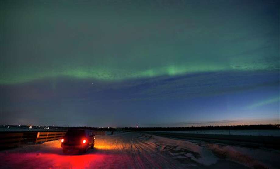 The aurora borealis, or northern lights, fill the sky early Sunday, March 17, 2013, above a motorist stopped in a roadside scenic pullout in Kenai, Alaska. The bright display at times filled the sky. Photo: M. SCOTT MOON, AP / AP