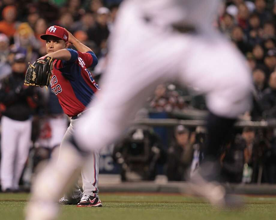 Puerto Rico pitcher Mario Santiago throws out a runner at first against Japan in the World Baseball Classic semi-final game in San Francisco on Sunday, March 17, 2013. Photo: Mathew Sumner, Special To The Chronicle