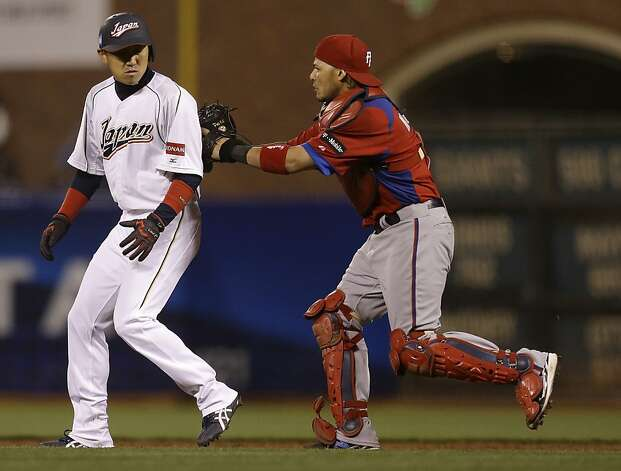 Japan's Seiichi Uchikawa is tagged out by Puerto Rico's Yadier Molina during a run down between first and second base during the eighth inning of a semifinal game of the World Baseball Classic in San Francisco, Sunday, March 17, 2013. Photo: Ben Margot, Associated Press