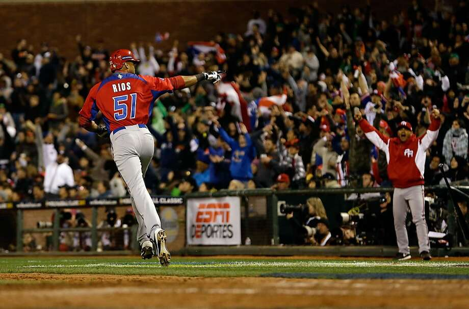 Alex Rios of Puerto Rico points to the bench after he hit a two run home run in the seventh inning of their game against Japan in the semifinals of the World Baseball Classic at AT&T Park on March 17, 2013 in San Francisco, California. Photo: Ezra Shaw, Getty Images