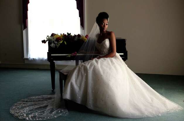Deja Jackson wears a modified sweetheart neckline tulle ball gown in blush with crystal and ribbon flower accents, $6,900 with a matching veil, $1,100, both by Christos at Julian Gold, (210) 824-2493. Pearl earrings, $36, from Bridal Salon of San Antonio, (210) 828-7931. Photo: Helen L. Montoya, San Antonio Express-News / ©2013 San Antonio Express-News