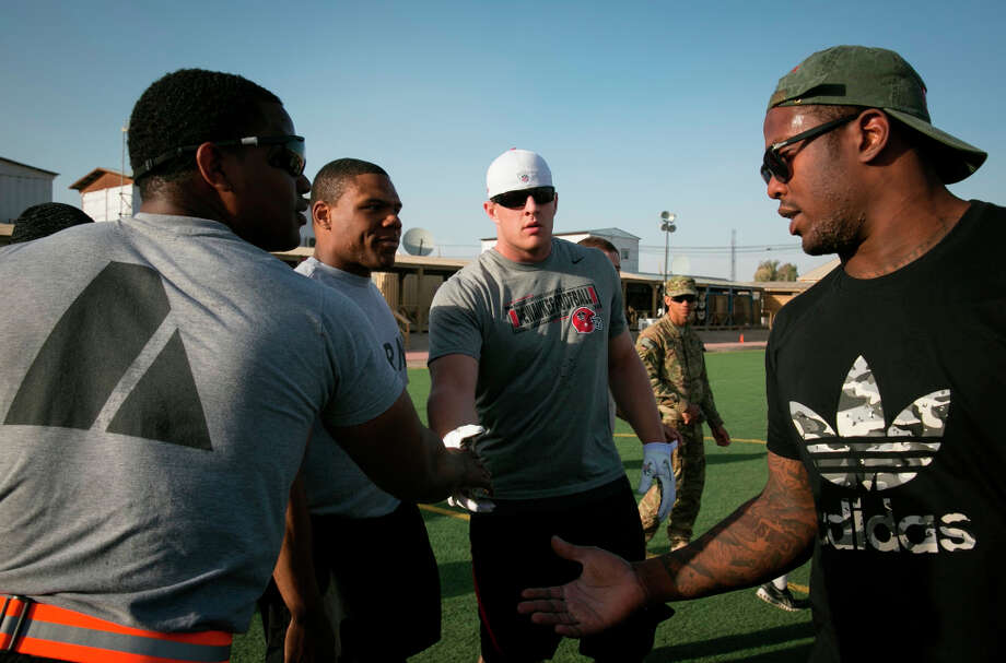 Texans defensive end J.J. Watt and Broncos linebacker Von Miller shake hands with soldiers stationed in the Middle East following an impromptu touch football game. / USO