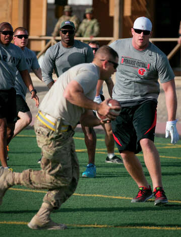 Texans defensive end J.J. Watt tries to stop a service member during an impromptu touch football game. Photo: Fred Greaves / USO