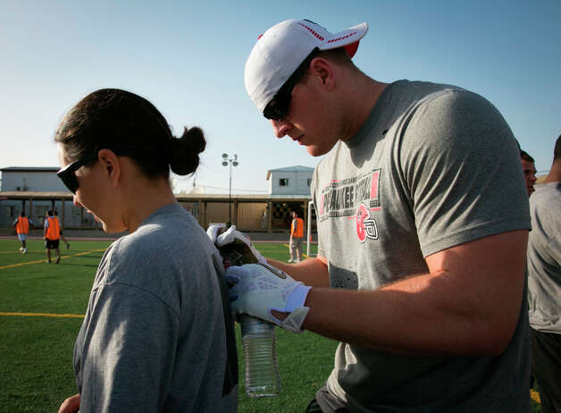 Texans defensive end J.J. Watt autographs a shirt for a soldier stationed in the Middle East. / USO