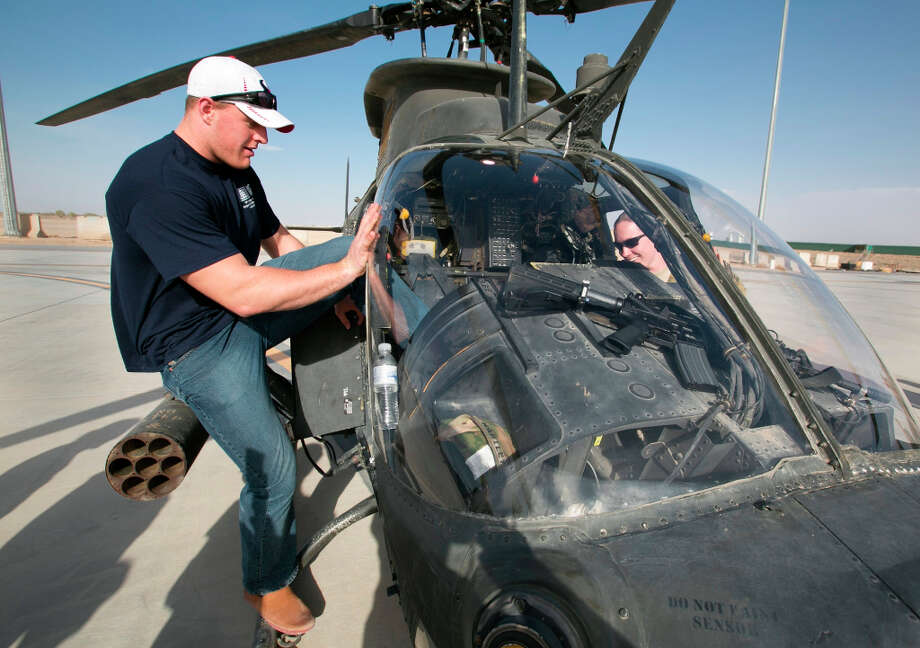 Texans defensive end J.J. Watt tries to squeeze into the cockpit of a Kiowa helicopter during a stop on his week-long USO/NFL tour in the Middle East. Photo: FRED GREAVES / USO
