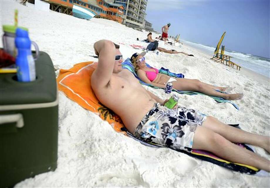 Hunter Mason, left, and Olivia Murat, on spring break from the University of Indianapolis, relax on the beach in Destin, Florida. (AP Photo/Northwest Florida Daily News, Nick Tomecek) Photo: Nick Tomecek, AP / Northwest Florida Daily News