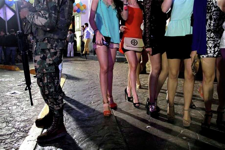 A Mexican navy marine stands guard as women walk by in an area of nightclubs during Spring Break in the resort city of Cancun, Mexico. (AP Photo/Israel Leal) Photo: Israel Leal, AP / AP2013