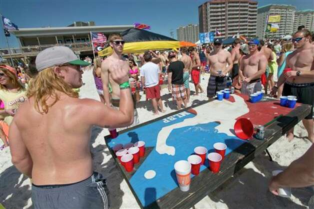 Rory Island, left, throws a ping-pong ball while playing beer pong with other spring breakers on the beach behind the Whale's Tail Restaurant in South Walton County, Florida on Wednesday, March 13, 2013. For the next few weeks thousands of college students will descend on this resort community in northwest Florida for the annual pilgrimage of spring break. Photo: DEVON RAVINE, AP / NORTHWEST FLORIDA DAILY NEWS