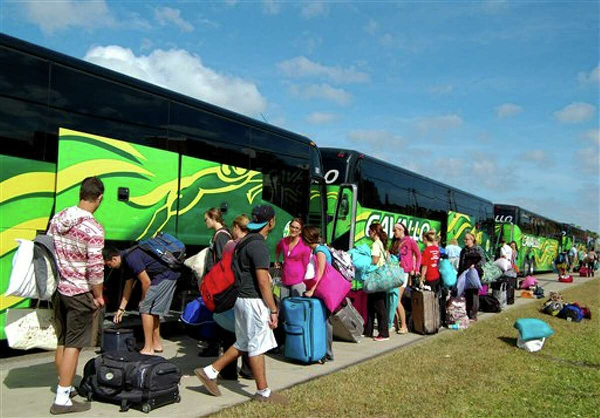 Spring breakers load their luggage onto charter busses to get ready to head back home to Chicago, Illinois on Friday, March 15, 2013 in South Padre Island, Texas.